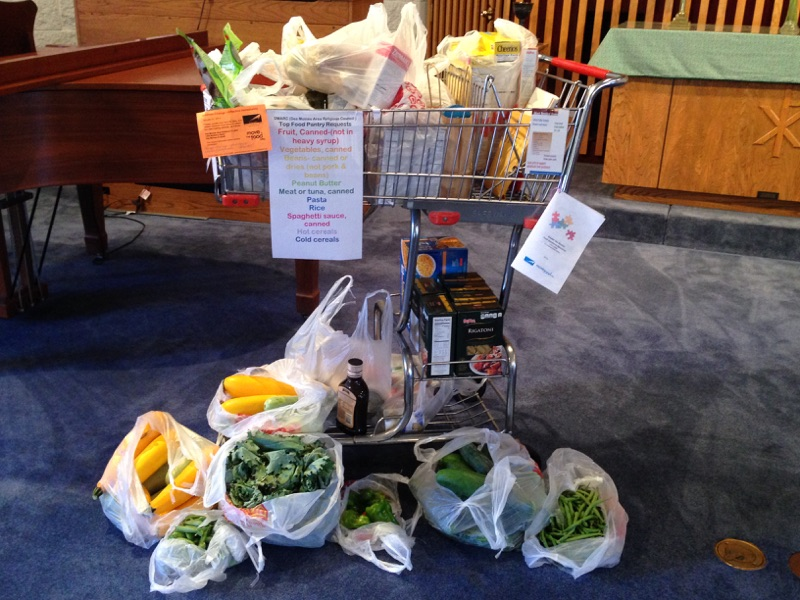a full grocery cart with bags of green and yellow produce at the bottom