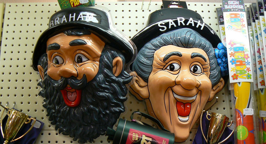 "Two plastic masks, one of a smiling bearded man with a hat that says Abraham, one of a grey-haired smiling woman with a hat labeled ""Sarah"""