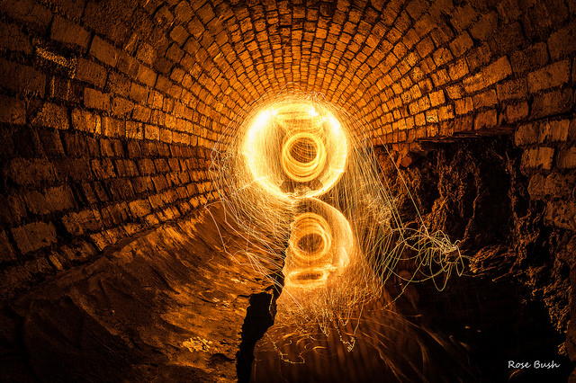 a glowing yellow circle lighting a tunnel of bricks