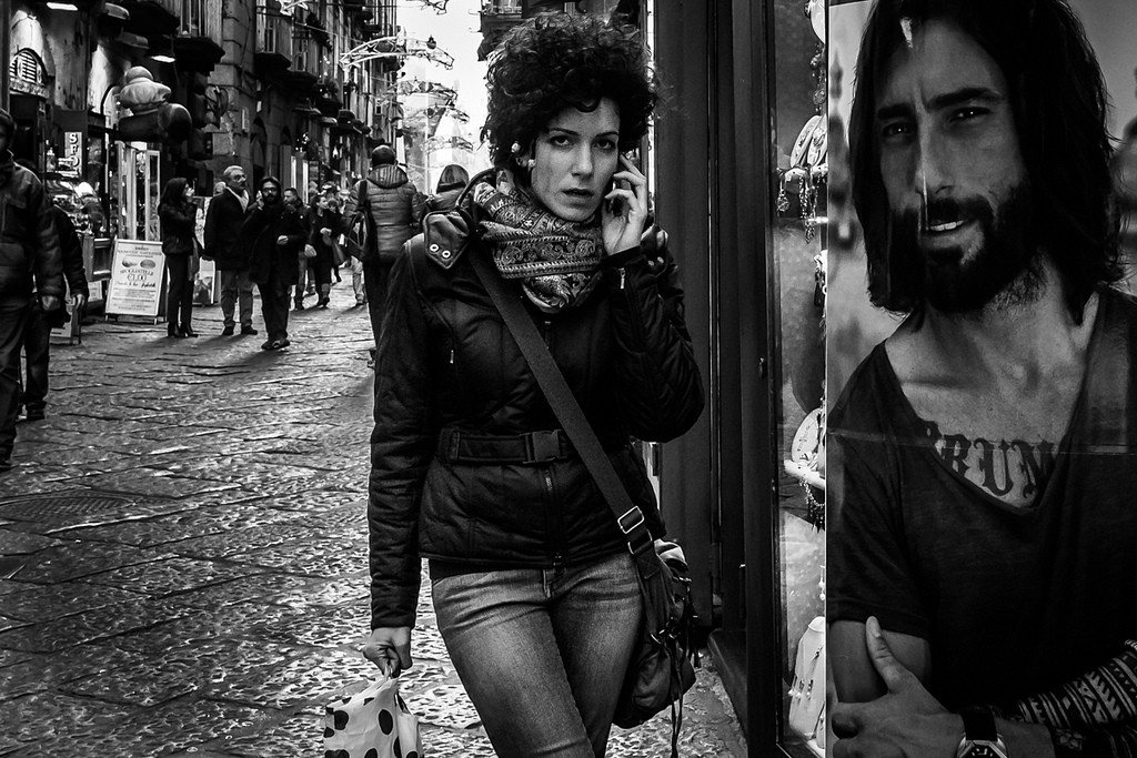 Black and white image of a woman with black hair holding a phone to her head while a street bustles behind her