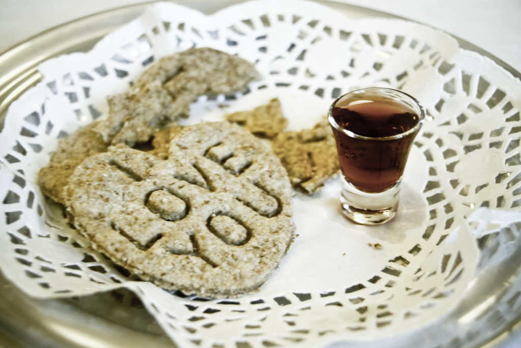 "a heart-shaped cookie saying ""I love you"" next to a small communion glass on a lace doily"