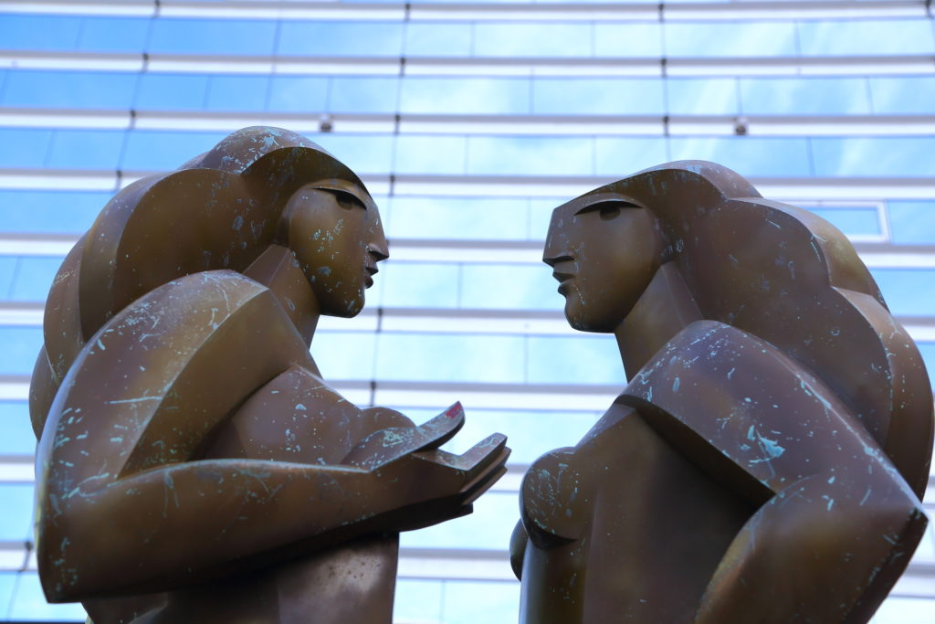 Two bronze statues of women in conversation