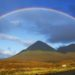 a ranbow high above mountains