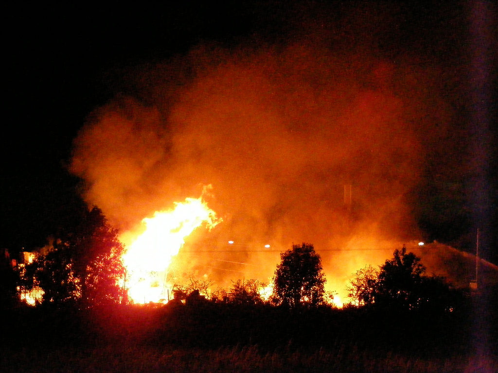 bright orange flames and tall smoke with blackened trees in foreground