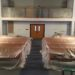 Two rows of pews covered in translucent plastic and a balcony railing also wrapped