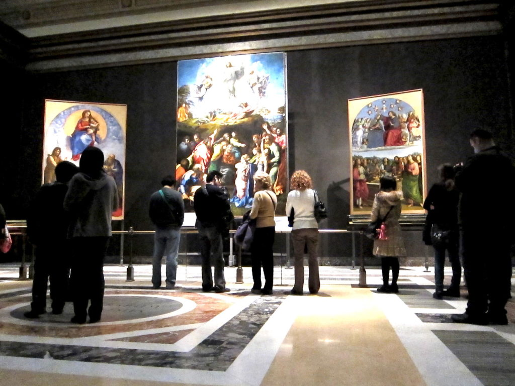 A group of people in front of three paintings in an art gallery. The center painting is an illustration of the Transfiguration with three figures in the top half and a bright cloud around them.