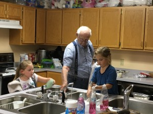 a 94 year-old man helps a 6 year-old and 7 year-old clean up
