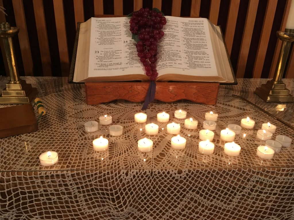 A bible with a bunch of grapes on it with tealights in front.